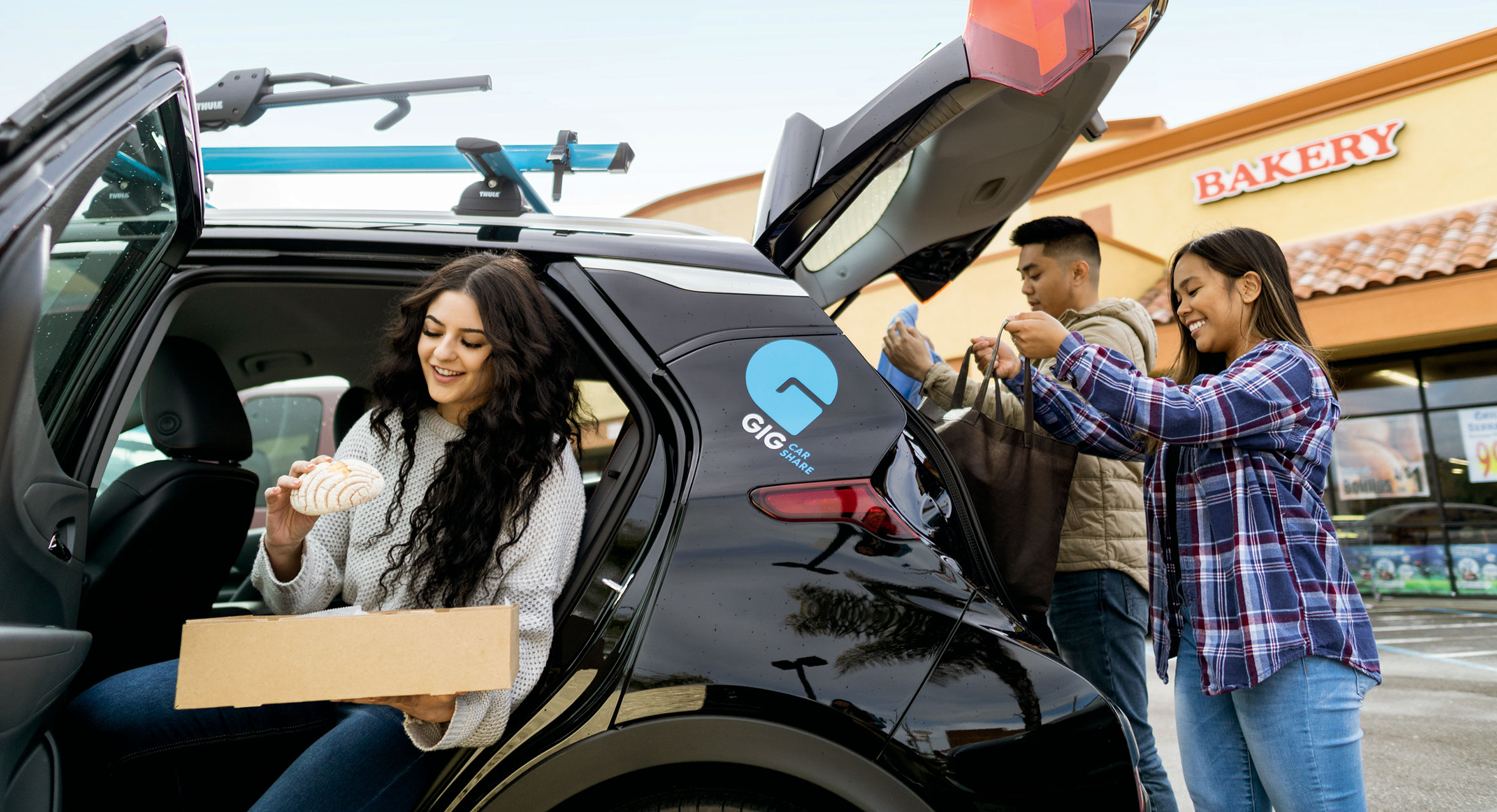 Three Friends With All Electric Gig Car Share Vehicle Load Up From Bakery Picture