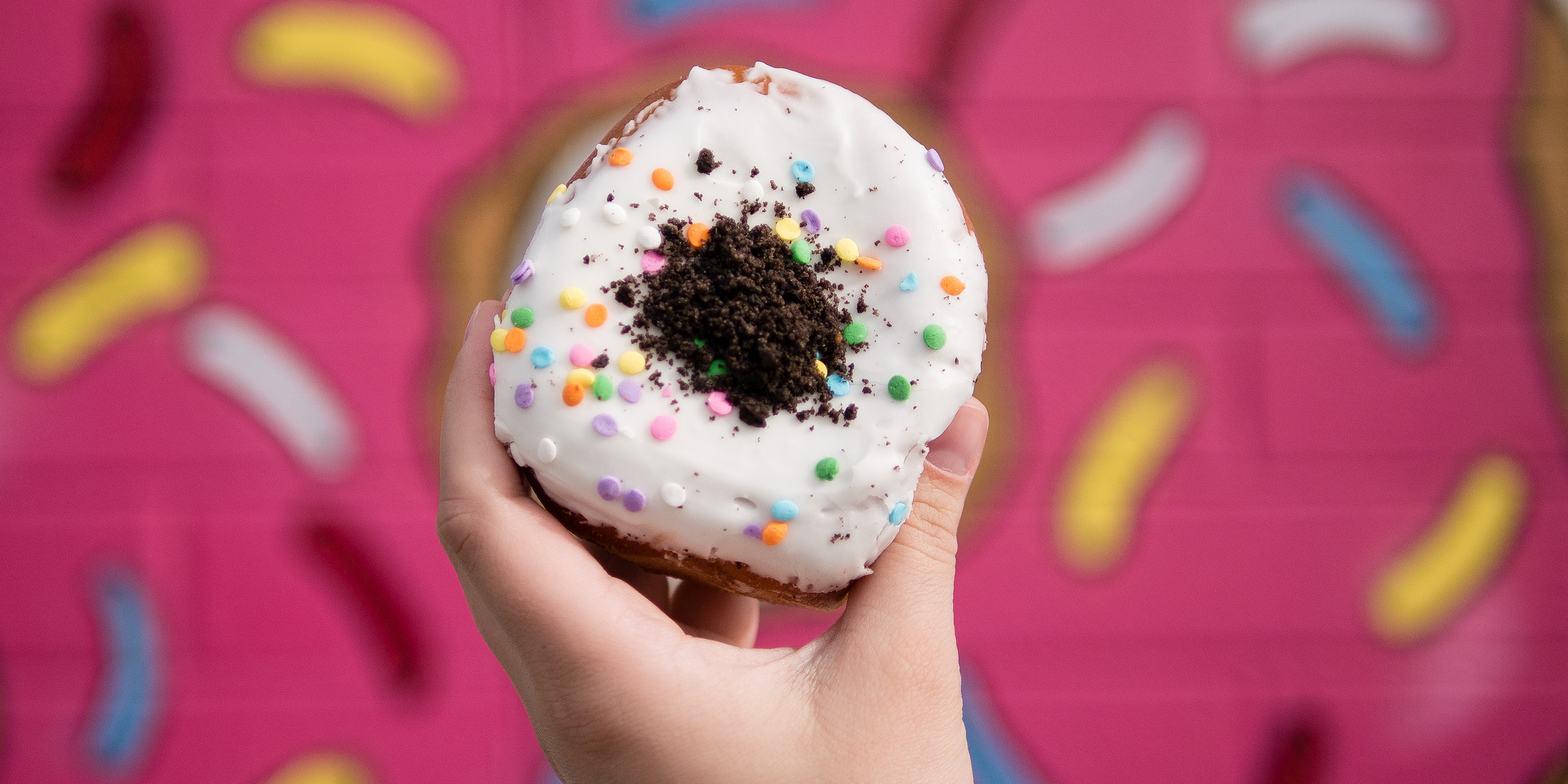 A Hand Holds Oh My Birthday Cake Oreo Stuffed Donut From The Las Vegas